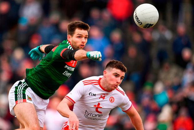Mayo's Ger Cafferkey punches the ball clear ahead of Connor McAliskey. Photo: Sam Barnes/Sportsfile