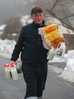 James Byrne from Kildare Civil Defence helps deliver bread and milk to people trapped by the snow in Kilteel, Co Kildare during Storm Emma. Picture: Damien Eagers
