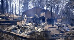 Smoke rises from a destroyed home after a bushfire swept through the town of Tathra, located on the south-east coast of New South Wales in Australia Photo: AAP/Dean Lewins/via Reuters