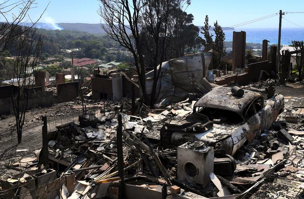 Smoke rises near a destroyed car and home after a bushfire swept through the town of Tathra, located on the south-east coast of New South Wales in Australia, March 19, 2018. AAP/Dean Lewins/via REUTERS