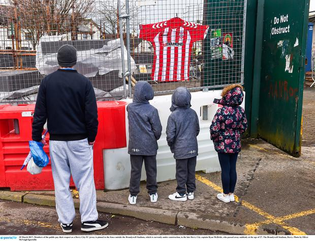 Members of the public pay their respect as a Derry City FC jersey is pinned to the fence outside the Brandywell Stadium