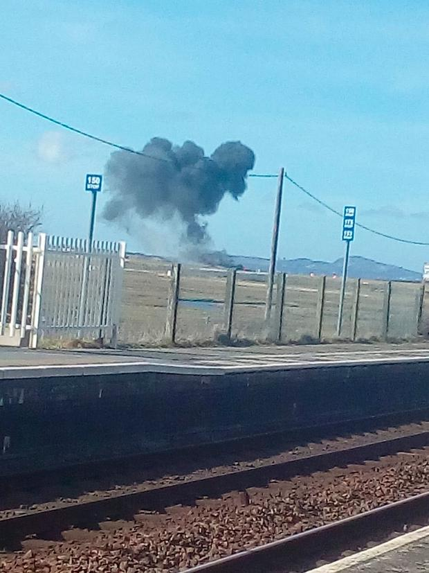 Smoke rises after a Royal Air Force Aerobatic Team, known as the Red Arrows, plane crashed in Valley, Anglesey, Wales, Britain March 20, 2018 in this image obtained from social media.