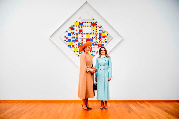 Dutch Queen Maxima and Queen Rania of Jordan pose in front of the work of art
