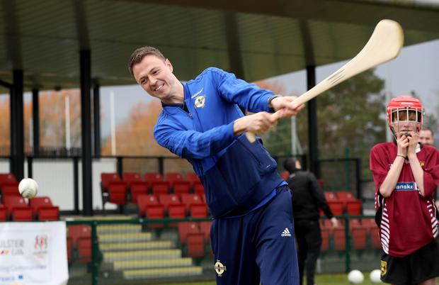 Northern Ireland defender Jonny Evans turns his hand to hurling during the launch of Sport Uniting Communities – a collaboration project between the Irish FA, Ulster GAA and Ulster rugby