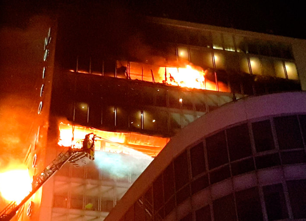Firefighters tackle the blaze as it rips through several floors of the building