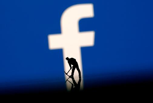 A figurine is seen in front of the Facebook logo in this illustration. REUTERS/Dado Ruvic/File Photo