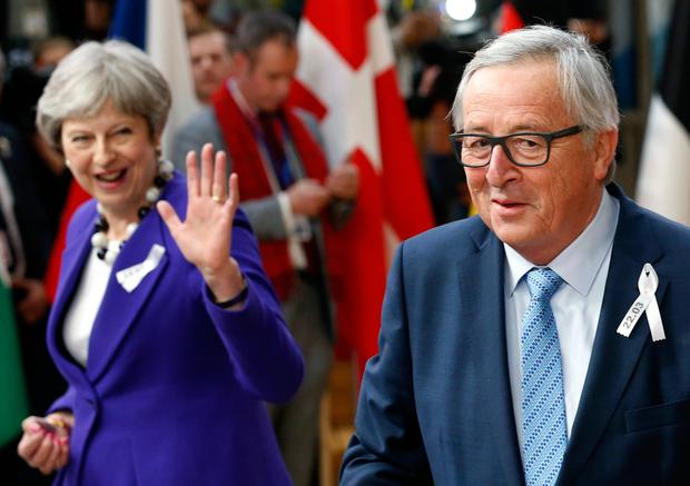 European Commission President Jean-Claude Juncker and Britain's Prime Minister Theresa May arrive at a European Union leaders' summit in Brussels yesterday. Photo: Reuters