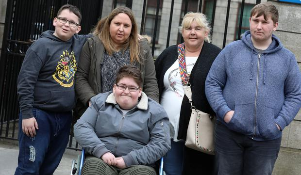 The Sweeney family (l-r)- James (11), (In wheelchair) Stephen (15) and Jason (17) pictured leaving the Four Courts with their mum, Michelle Sweeney (Second from left in pic) and their grandmother, Linda (second from right in pic) Picture: Collins Courts
