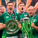 Jonathan Sexton (left) holds the Triple Crown and Ireland's hooker Rory Best (R) holds the Six Nations trophy as Ireland players celebrate their Six Nations Grand Slam victory after the Six Nations international match atTwickenham. Photo: Getty Images
