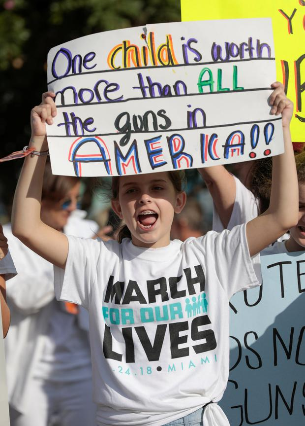 A girl holds a sign while rallying in the street during the