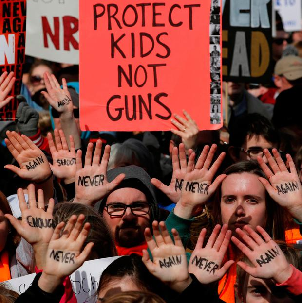 Participants carry signs and show slogans on their hands as students and gun control advocates hold the