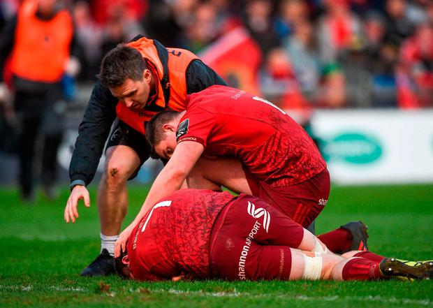 Ian Keatley and Munster physio Damien Mordan check on the injured Tommy O'Donnell at Thomond Park on Saturday. Photo: Diarmuid Greene/Sportsfile