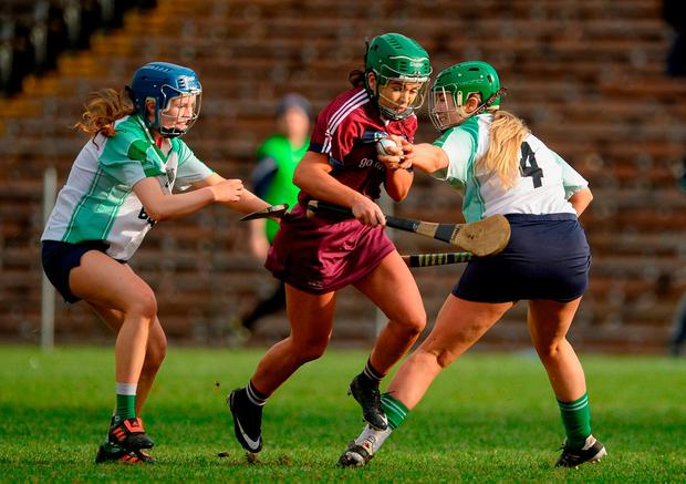 Slaughtneil's Shannon Graham muscles her way through a challenge from Erica Leslie and Aisling Spellman of Sarsfields. Photo: Oliver McVeigh/Sportsfile