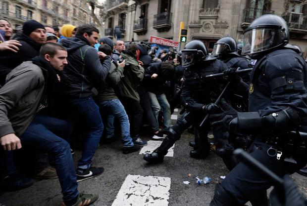 Catalan Mossos d'Esquadra regional police officers clash with pro-independence supporters trying to reach the Spanish government office in Barcelona, Spain, Sunday, March 25, 2018. (AP Photo/Emilio_Morenatti)
