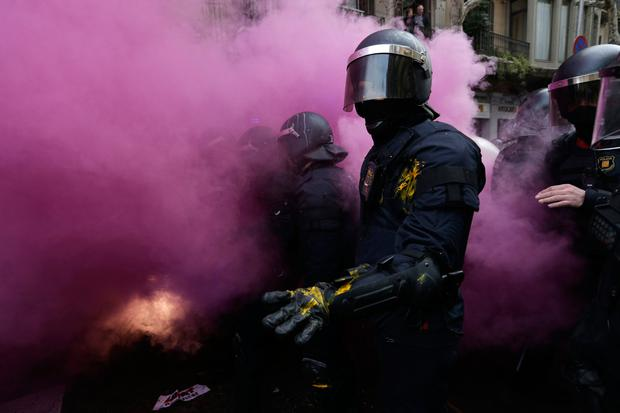Catalan Mossos d'Esquadra regional police officers stand amid smoke from a smoke bomb during clashes with pro-independence supporters trying to reach the Spanish government office in Barcelona, Spain, Sunday, March 25, 2018. (AP Photo/Emilio_Morenatti)