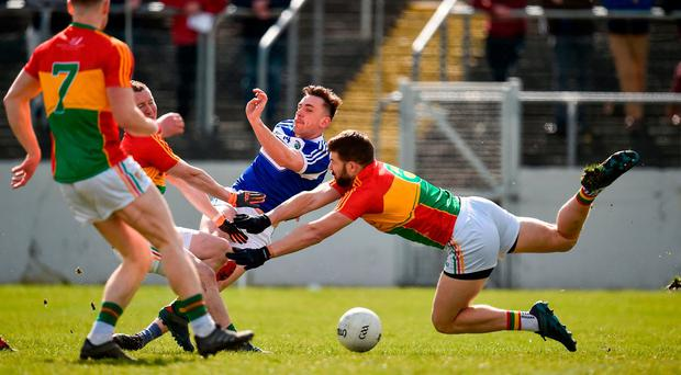 Gary Walsh squeezes home the Laois goal despite pressure from Carlow's Danny Moran and Daniel St Ledger. Photo: Seb Daly/Sportsfile