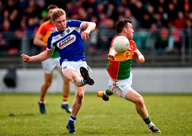 Alan Farrell of Laois kicks a point under pressure from Darragh Foley. Photo: Seb Daly/Sportsfile
