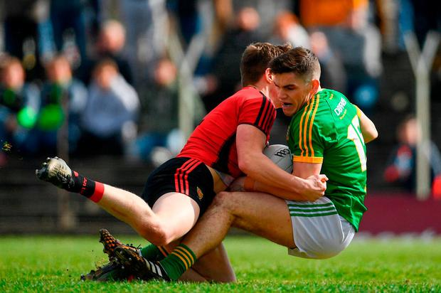 Anthony Doherty of Down brings down Meath's Donal Lenihan, resulting in a penalty for the Royals. Photo: Ramsey Cardy/Sportsfile