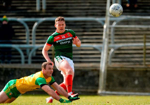 Andy Moran sends the ball forward despite the efforts of Neil McGee. Photo: Oliver McVeigh/Sportsfile