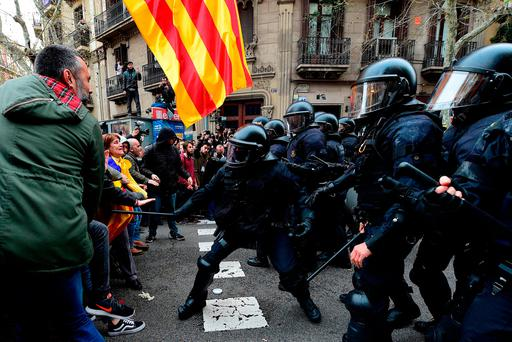 Protesters scuffle with riot police in Barcelona yesterday as marchers protest Mr Puigdemont's arrest. Photo: AFP/Getty