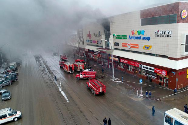 In this Russian Emergency Situations Ministry photo on Sunday, March 25, 2018, smoke rises above a multi-story shopping center in the Siberian city of Kemerovo, about 3,000 kilometers (1,900 miles) east of Moscow, Russia. (Russian Ministry for Emergency Situations photo via AP)