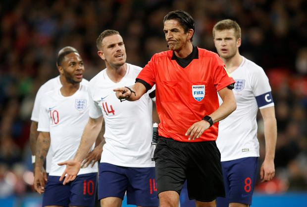 England's Jordan Henderson remonstrates with referee Deniz Aytekin after he awarded a penalty to Italy following a VAR decision. Photo: Reuters