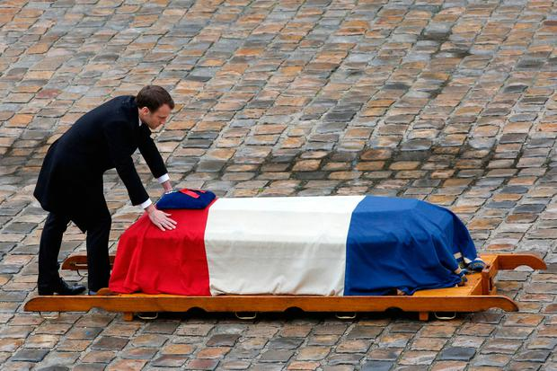 French President Emmanuel Macron leans at the coffin of Lt Co. Arnaud Beltrame after he was posthumously awarded the Legion of Honour yesterday at the Hotel des Invalides in Paris. Photo Christophe Ena:AP