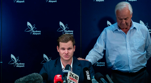 An emotional Steve Smith is comforted by his father Peter as he faces the media at Sydney International Airport. Photo: Brook Mitchell/Getty Images