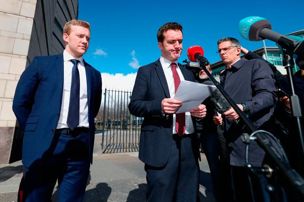 Stuart Olding (left) looks on as his solicitor Paul Dougan (centre) speaks to the media outside Belfast Crown Court after the verdict on Wednesday. Photo: PA