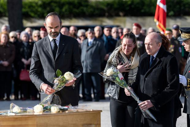 A daughter, second right, no name given, of victim Christian Medves reacts with French Interioir Minister Gerard Collomb, right, by father's coffin during a ceremony for three victims of last week's extremist gun rampage Photo: (AP Photo/Fred Lancelot)