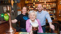 Maura Hallinan is joined by publicans Caroline Craughann and Stephen Hackett, her grandson, to pour the first pint at Nana's on Douglas Street in Cork. Picture: Provision