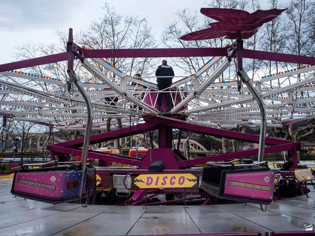 Policemen inspect a damaged fairground ride after an accident that killed one man and seriously wounded another person, in Neuville sur Saone, a small town north of Lyon, central France, Saturday, March 31, 2018. The Rhone prefecture said three other people were slightly injured. (AP Photo/Laurent Cipriani)