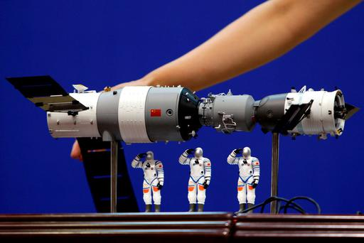 A model of the Tiangong-1 space lab module (L), the Shenzhou-9 manned spacecraft (R) and three Chinese astronauts is displayed during a news conference at Jiuquan Satellite Launch Center, in Gansu province, China June 15, 2012. REUTERS/Jason Lee/File Photo
