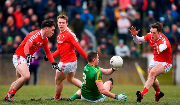 Bryan Menton feels the pressure from Louth players Derek Maguire, left, and Declan Byrne. Photo: Ramsey Cardy/Sportsfile