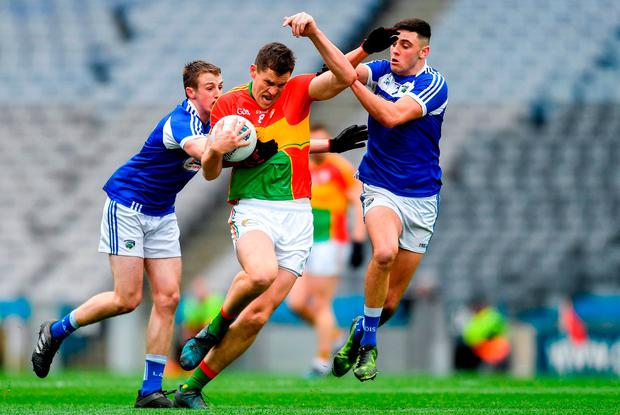 Carlow's Brendan Murphy feels the pressure from Benny Carroll, left, and Robert Pigott. Photo: Piaras Ó Mídheach/Sportsfile