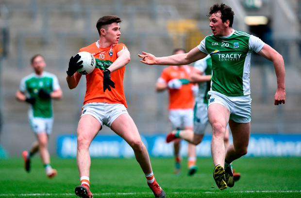 Armagh's Ben Crealey dodges a tackle from Tom Clarke. Photo: David Fitzgerald/Sportsfile