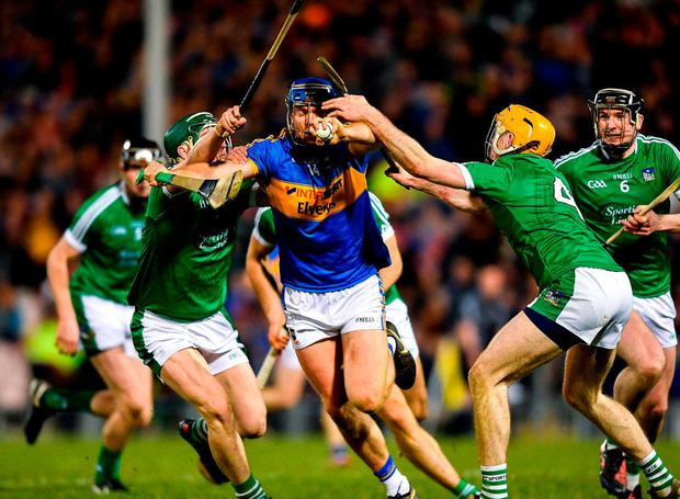 Tipperary's Jason Forde is tackled by Limerick's Sean Finn, left, and Richie English. Photo: Eóin Noonan/Sportsfile
