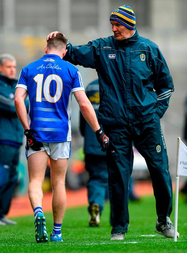 Cavan's Dara McVeety is consoled by Roscommon selector Liam McHale after leaving the field with an injury. Photo: Piaras Ó Mídheach/Sportsfile