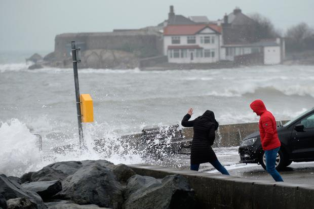 Walkers brave the massive waves yesterday at Sandycove, Co Dublin. Photo: Justin Farrelly