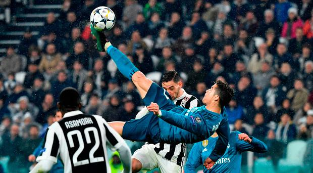 Real Madrid's Portuguese forward Cristiano Ronaldo (C) scores during the UEFA Champions League quarter-final first leg football match between Juventus and Real Madrid at the Allianz Stadium in Turin on April 3, 2018. / AFP PHOTO / Alberto PIZZOLIALBERTO PIZZOLI/AFP/Getty Images