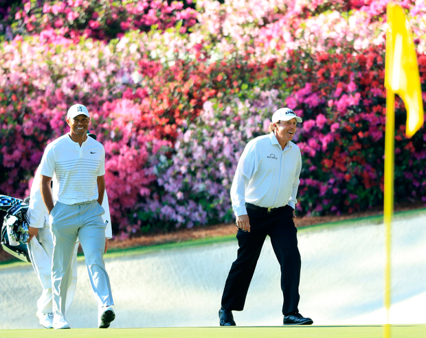 Tiger Woods and Phil Mickelson (R) are full of smiles as they walk onto the 13th green during a practice round at Augusta yesterday. Photo: Getty Images