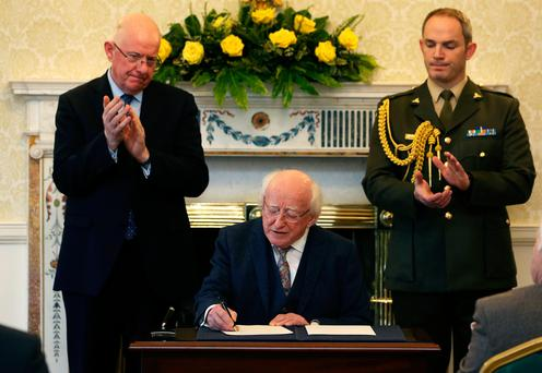 President Michael D Higgins (centre) along with Minister for Justice Charlie Flanagan (left) signs a warrant at Aras an Uachtarain, Dublin, granting a posthumous pardon for Myles Joyce in respect of his conviction for the notorious 1882 Maamtrasna murder case. Photo: Brian Lawless/PA Wire