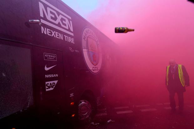 Bottles and cans are thrown at the Manchester City bus as it makes its way to Anfield. Photo: Paul Ellis/AFP/Getty Images