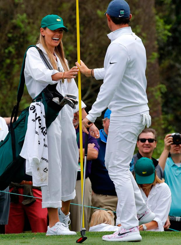 Rory McIlroy of Northern Ireland hands a pin marker to his wife Erica Stoll during the par 3 contest held on the final day of practice for the 2018 Masters golf tournament at Augusta National Golf Club in Augusta, Georgia, U.S. April 4, 2018. REUTERS/Mike Segar