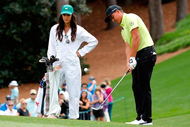 Rickie Fowler of the U.S. chips onto the first green as his girlfriend Allison Stokke watches during the par 3 contest held on the final day of practice for the 2018 Masters golf tournament at Augusta National Golf Club in Augusta, Georgia, U.S. April 4, 2018. REUTERS/Mike Segar
