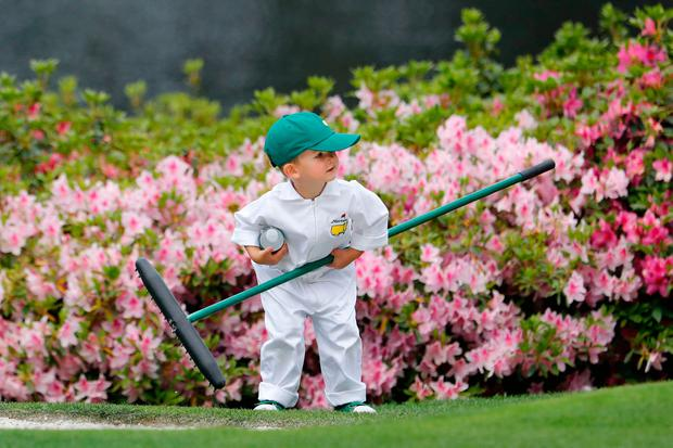 U.S. golfer Kevin Chappell's son Wyatt pucks up a rake as his father participates in the par 3 contest held on the final day of practice for the 2018 Masters golf tournament at Augusta National Golf Club in Augusta, Georgia, U.S. April 4, 2018. REUTERS/Jonathan Ernst