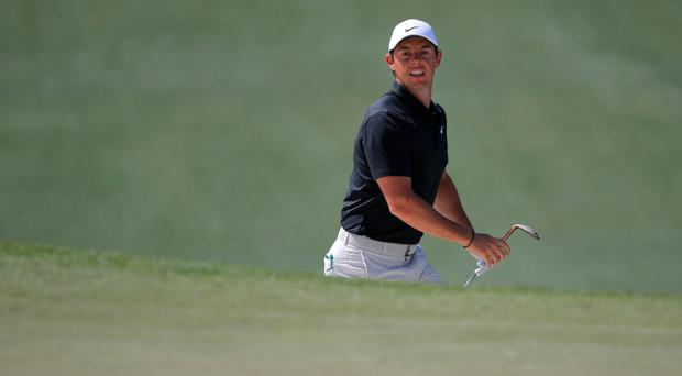 Rory McIlroy keeps a close eye on his bunker shot on the par-four seventh hole. Photo: Brian Snyder