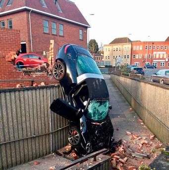 This Porsche 911 Targa 4S was left resting on its bonnet and almost vertical following the accident in Colchester's Crouch Street Thursday after the 73-year-old driver crashed through a car park wall and on to the footpath below. PC Turner / Essex Police/PA Wire
