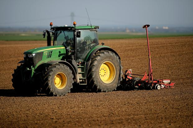 A farmer operates a tractor and a seeder in his field to sow sugar beets in the village of Cramoisy, France, March 27, 2017. REUTERS/Benoit Tessier/File Photo