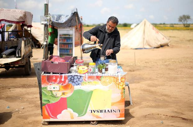 A Palestinian man sells tea and coffee during a tent city protest at Israel-Gaza border, in the southern Gaza Strip April 3, 2018. Picture taken April 3, 2018. REUTERS/Ibraheem Abu Mustafa